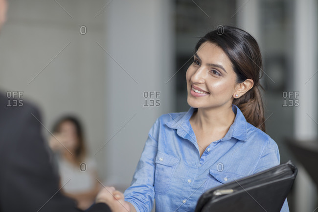 Smiling woman in office shaking hands