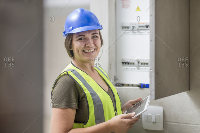 Portrait of smiling female electrician with tablet at fuse box