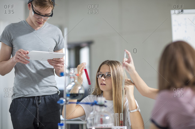 Students in science class with test tubes and tablet