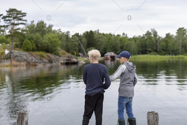 Boys fishing at lake - Offset