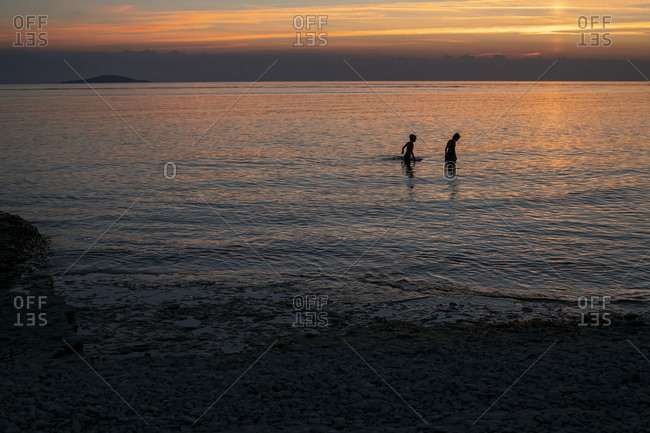 People in sea at sunset