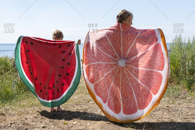 Kids holding beach towels with fruit pattern