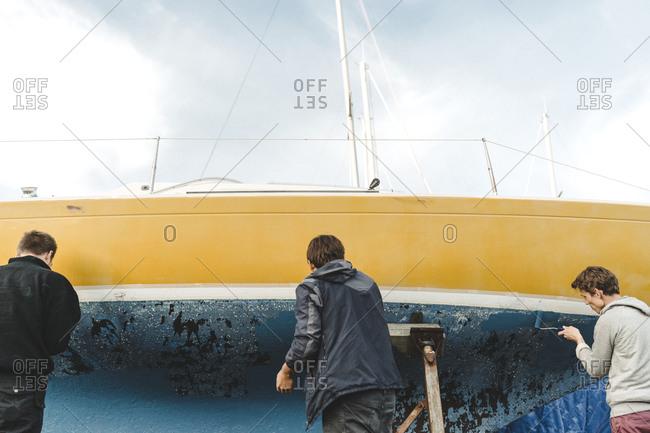 Men sticking masking tape on boat