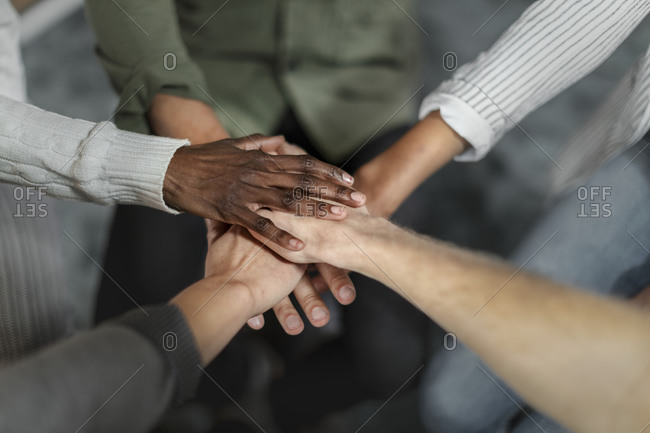 Closeup shot of group of unrecognizable people joining their hands together in huddle