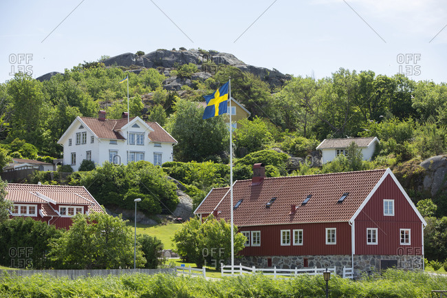 Swedish flag in front of wooden house