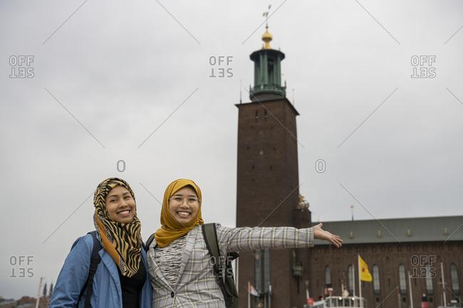 Female friends looking at camera, Stockholm City Hall on background, Stockholm, Sweden