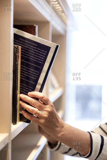 Hand taking book from shelf