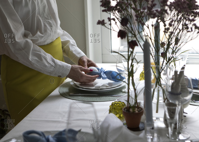 Mid section of woman preparing Easter place setting