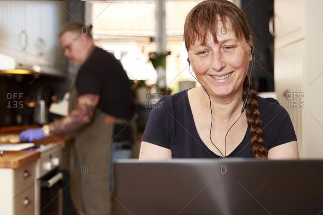 Smiling woman using laptop - Offset