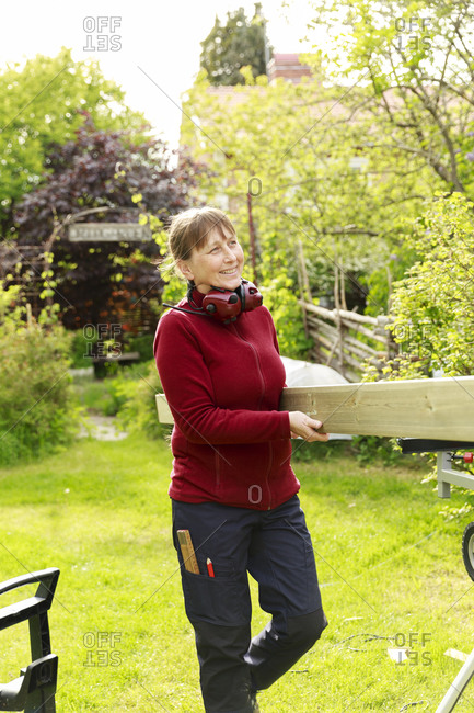 Woman in garden carrying plank