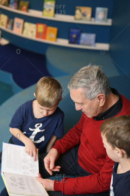 Grandfather reading to grandsons in library