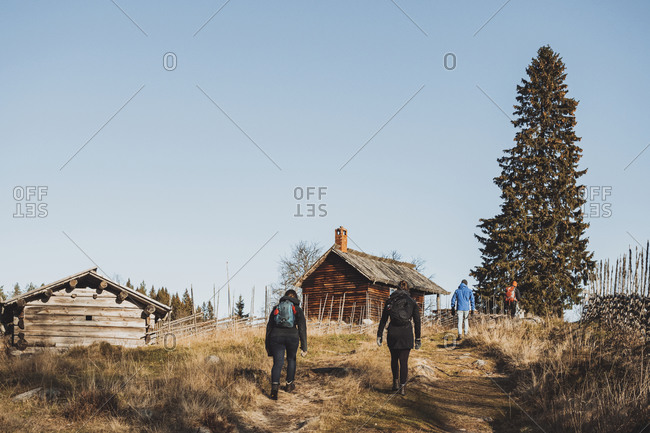 People hiking towards wooden cottages