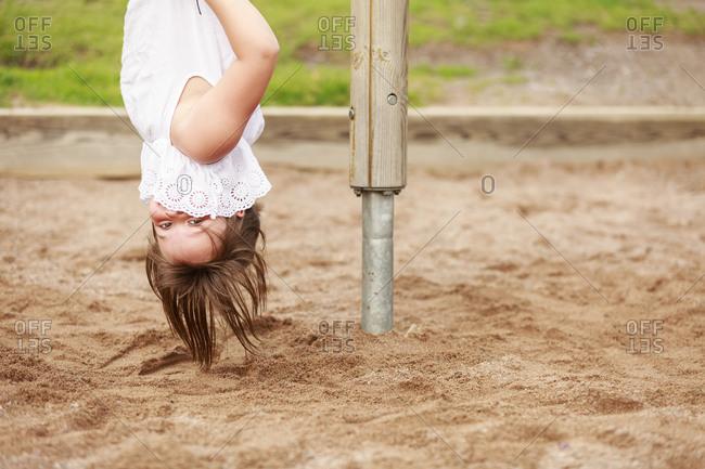 Girl hanging upside down and looking at camera