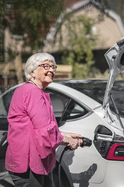 Smiling woman charging electric car