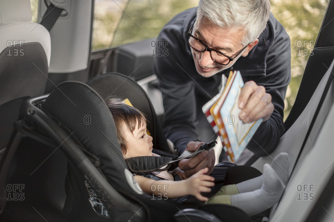 Grandfather fastening baby girl into car safety seat