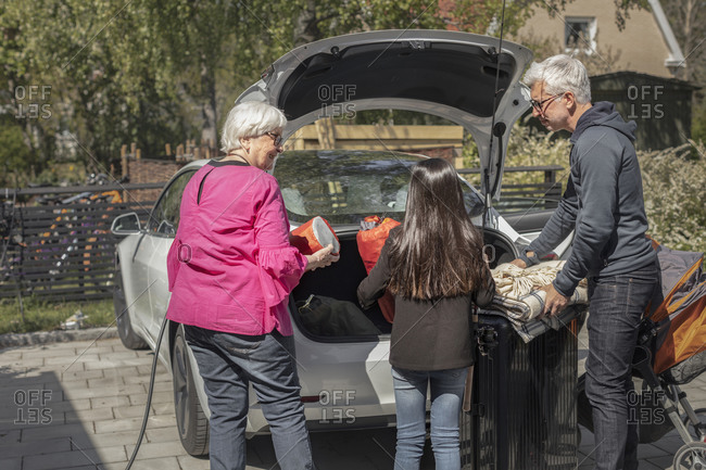 Grandparents with granddaughter loading car