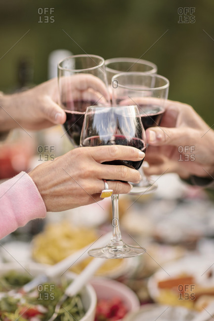 People clinking red wine glasses