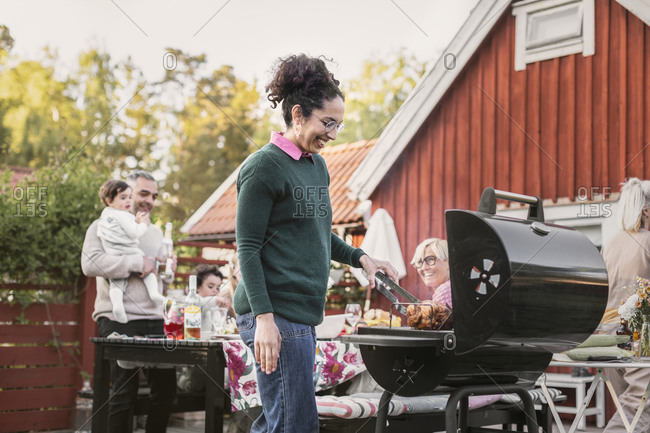 Smiling woman preparing food on barbecue