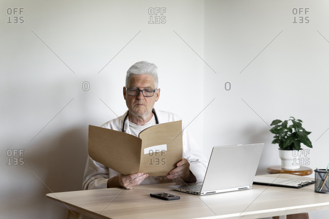 Senior doctor examining medical record while sitting at desk in clinic