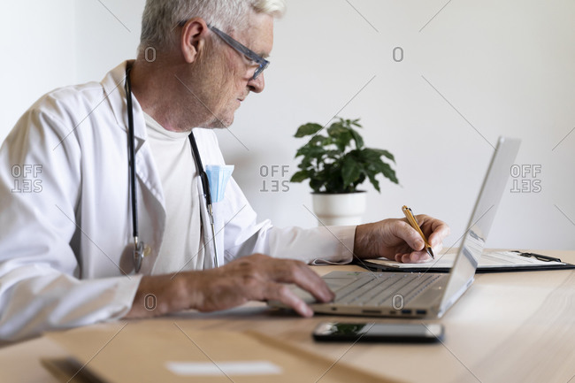 Senior doctor working on laptop while sitting in his clinic