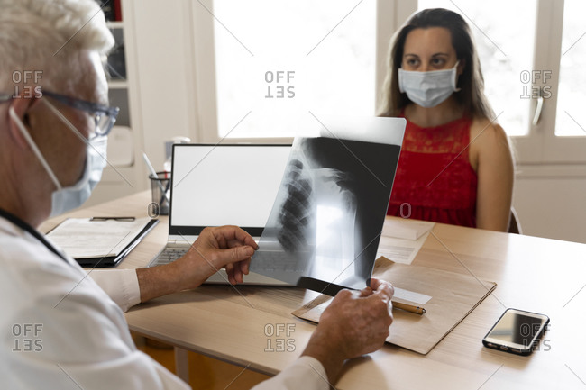 Doctor looks at medical x-ray of human neck while sitting in clinic