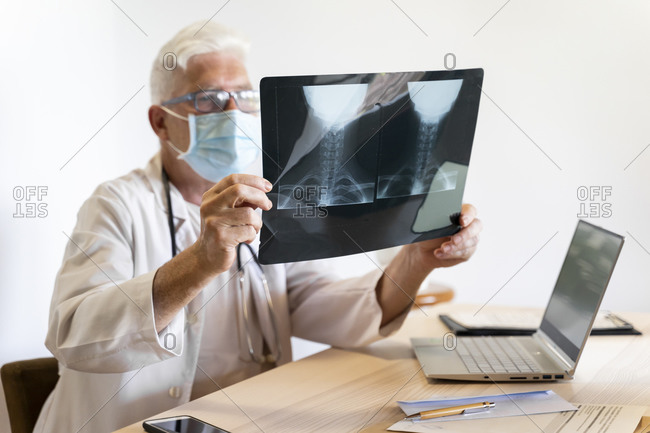 Doctor examining medical x-ray of human neck while sitting in clinic