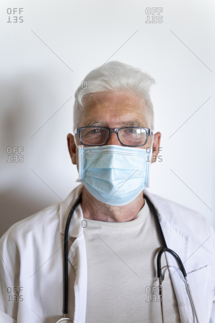 Senior doctor wearing surgical mask on face standing against wall