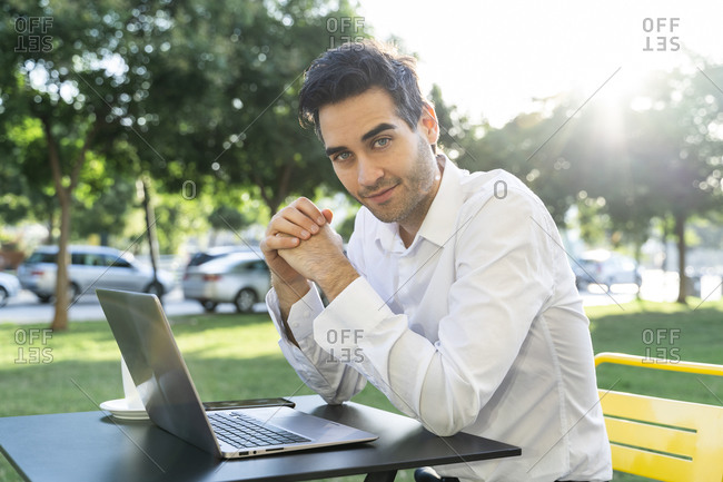 Handsome businessman with hands clasped sitting at sidewalk cafe