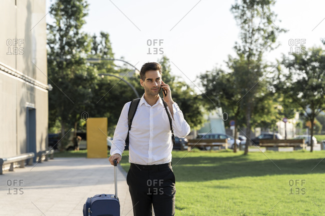 Businessman with suitcase talking over smart phone while walking on footpath