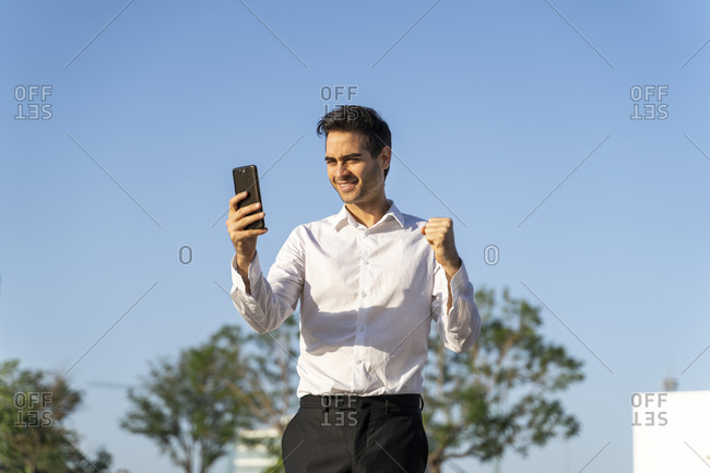 Happy businessman gesturing while using smart phone against clear blue sky
