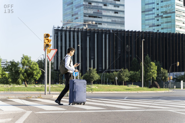 Businessman with suitcase using smart phone while crossing road in city