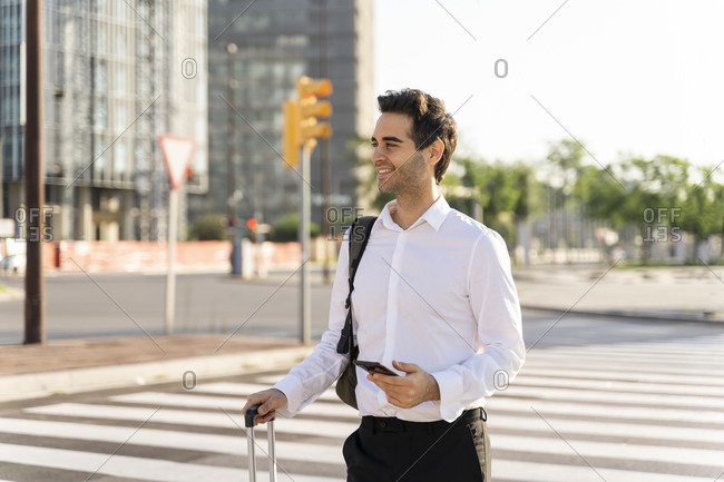 Smiling businessman holding smart phone and suitcase looking away while standing on street in city