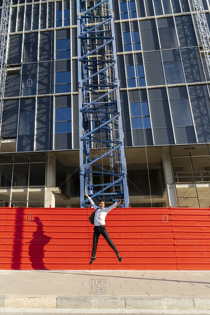 Cheerful businessman with arms raised jumping on footpath against built structure