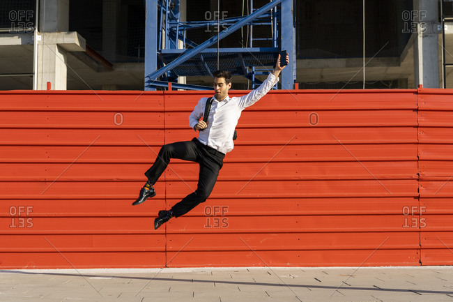 Cheerful male entrepreneur with arm raised jumping on footpath against built structure