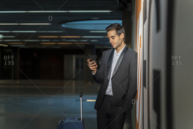 Male professional using mobile phone while standing with suitcase by wall at station