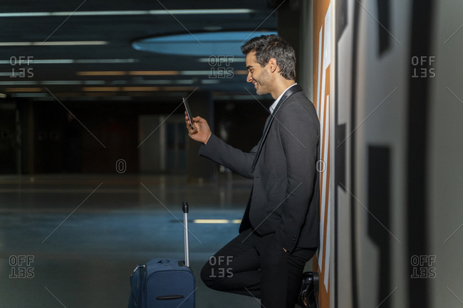 Smiling male entrepreneur using mobile phone while standing with suitcase by wall at station