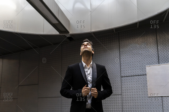 Thoughtful male professional wearing suit looking through skylight at station