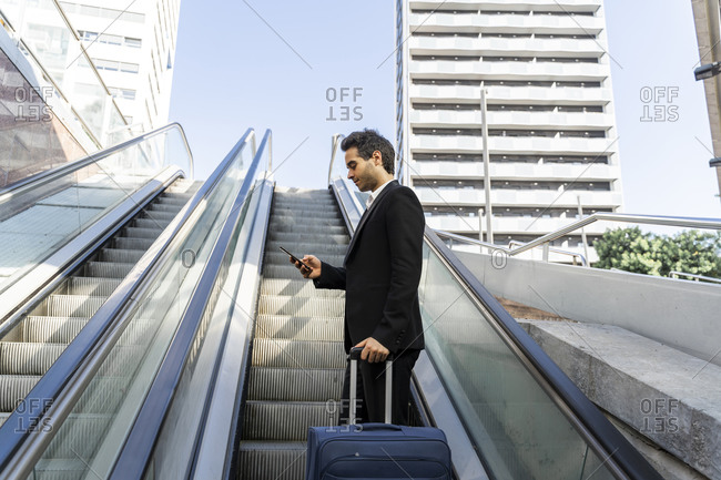Businessman with suitcase using smart phone while standing on escalator in city