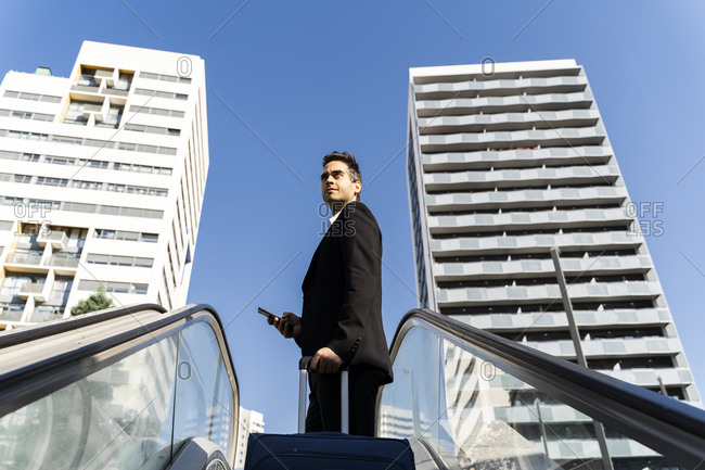 Businessman with suitcase looking away while standing on escalator against clear sky in city