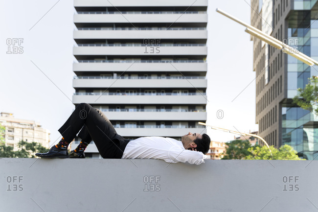 Thoughtful businessman with hands behind head lying on retaining wall in city