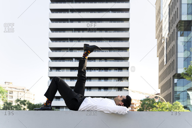 Businessman with foot up lying on retaining wall against modern building in city