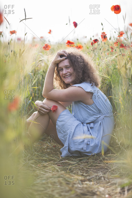 Smiling young woman with hand in hair sitting in poppy field