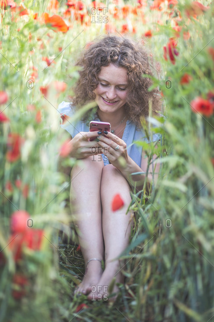 Young woman using mobile phone while sitting in agricultural field