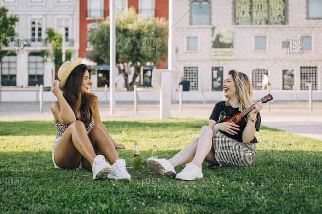 Cheerful woman playing ukulele while sitting with female friend on grassy land