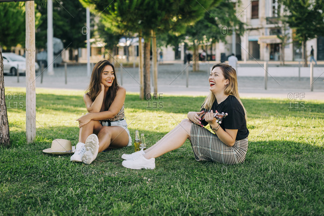 Young woman looking at carefree friend playing ukulele while sitting on grassy land