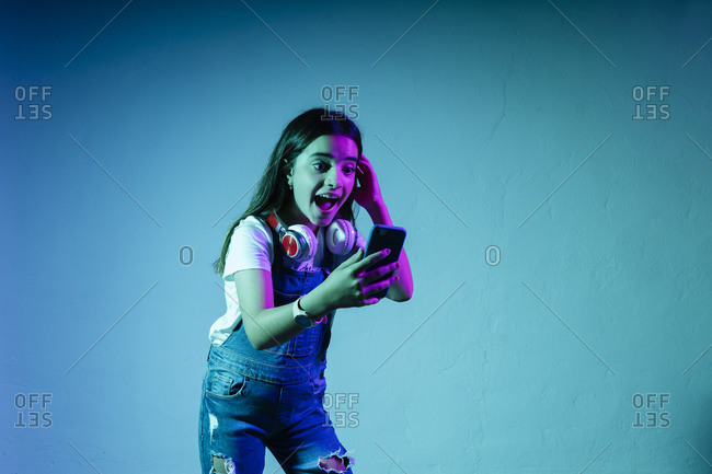 Excited girl looking at smart phone while standing against blue background