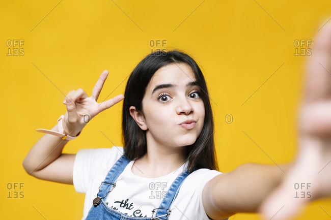 Girl showing peace sign while standing against yellow background