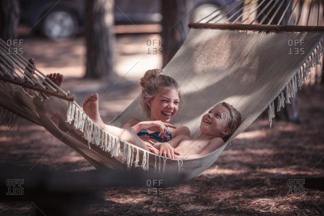 Happy girls relaxing on hammock at beach during summer