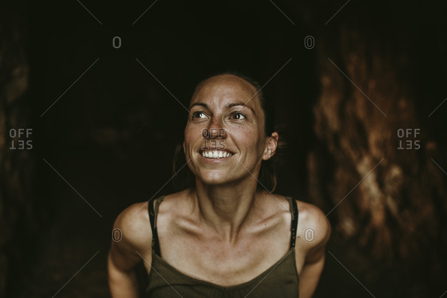 Smiling female trekker standing in cave