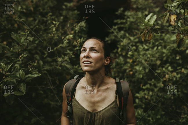 Thoughtful woman explorer standing in forest